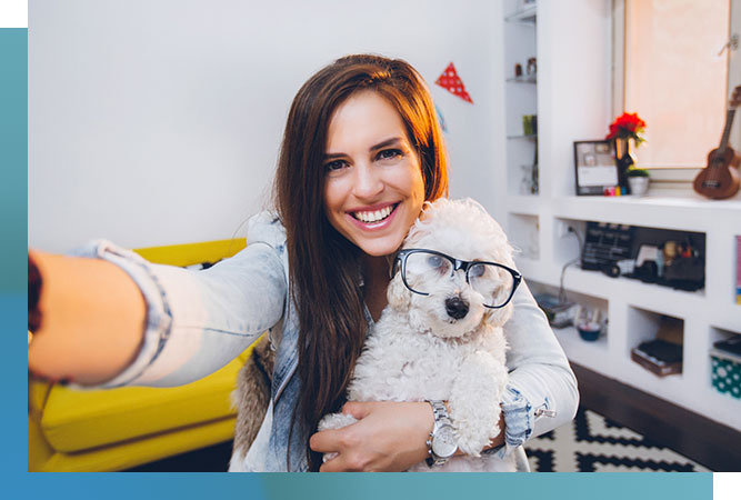 girl holding a white dog with glasses